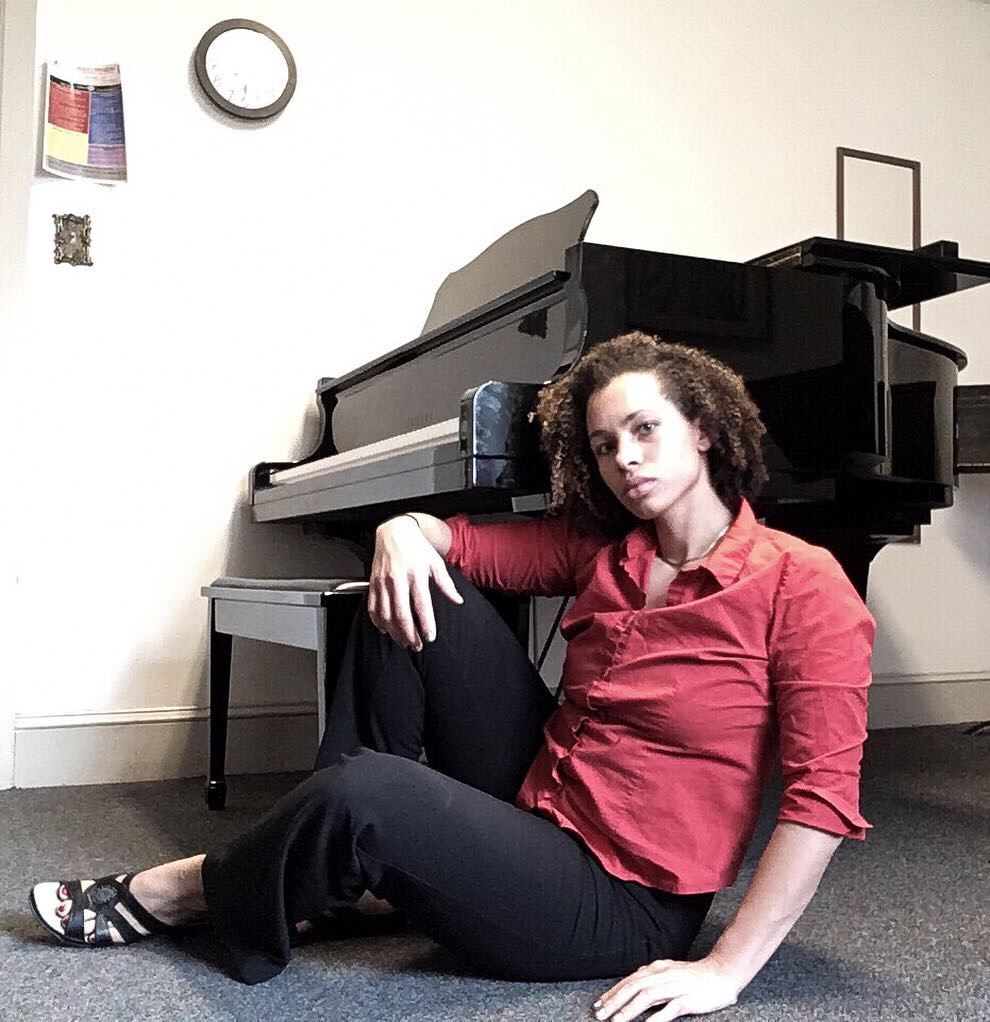 Jones half seated reclining in front of a piano. her right hand rests atop her knee